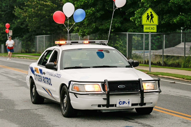 A police car with balloons tied to it drives down the street